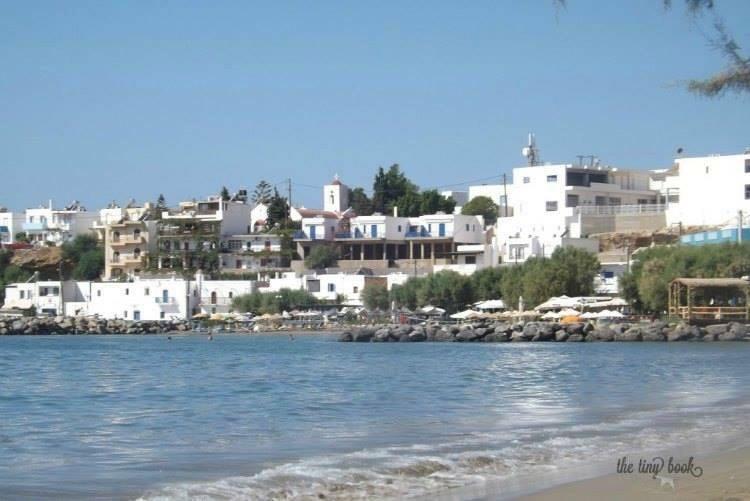 Coastline of Makrigialos, beach and sea. White houses in the background.