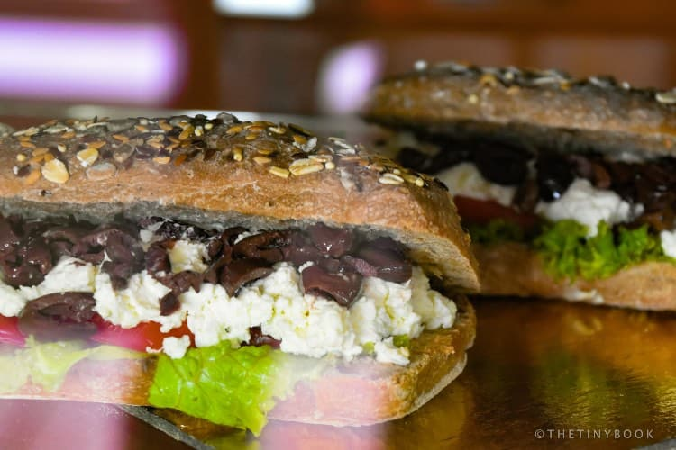 Whole flour bread with typical Greek ingredients: olives, tomato, and soft myzithra cheese.