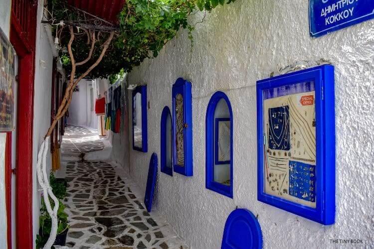 narrow passage, blue frames on the wall, shops Naxos island
