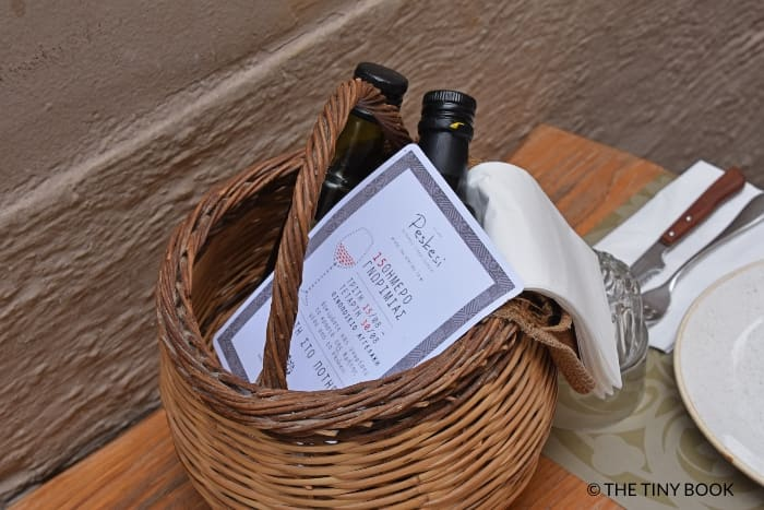 Basket with olive oil and wine list, Peskesi restaurant, Heraklion, Crete.