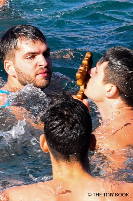 Two Greeks kissing the cross rescued from the sea during the Greek Christmas tradition called Epiphany