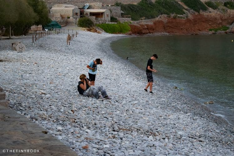 The kids and me taking pictures of Spinalonga island, on the pebble beach of Plaka.