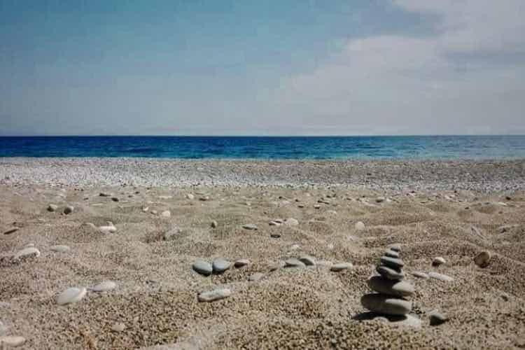 Stones piled on the beach on Glyka nera beach (Sfakia region, Crete)