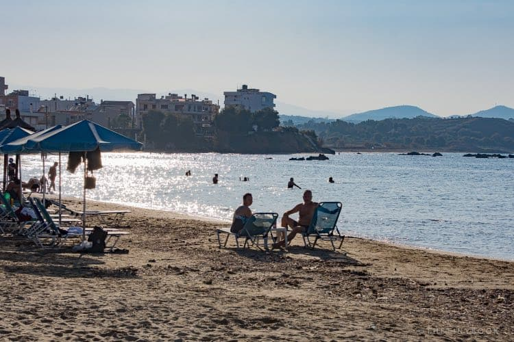 people sitting by the sea, on the beach of Neach Chora, Crete.